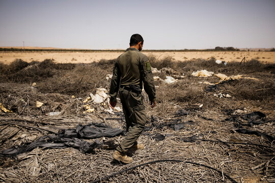 An Israeli soldier surveys the area after a Syrian missile exploded in southern Israel, the Israeli military said, near Ashalim