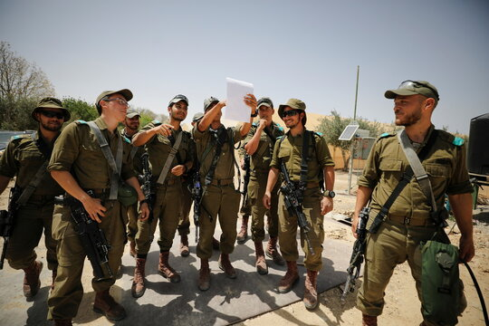 Israeli soldiers gather as they survey the area after a Syrian missile exploded in southern Israel, the Israeli military said, in Ashalim