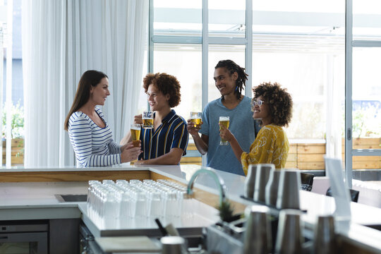 Diverse group of male and female colleagues laughing and having beer at bar
