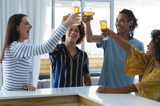 Diverse group of male and female colleagues raising glasses of beer at bar