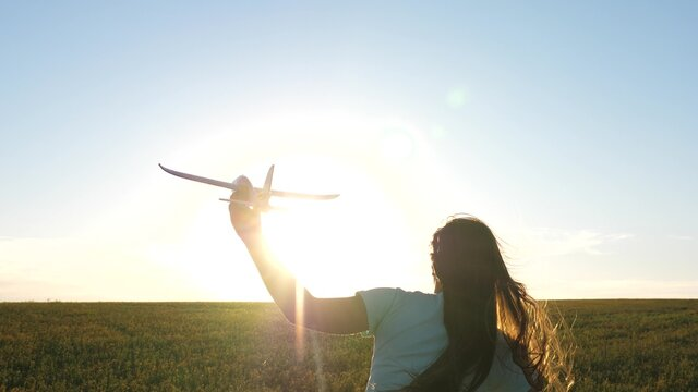 Happy girl runs with toy airplane across field in rays of sunset. Childrens play in toy airplane. Teenager dreams of flying and becoming pilot. Girl wants to become pilot and an astronaut. Slow motion
