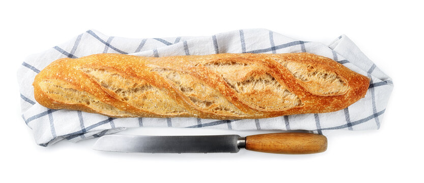 Sourdough baguette with knife isolated on white background, top view.