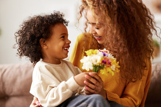 Cute little son giving flower bouquet his mom for Mothers day