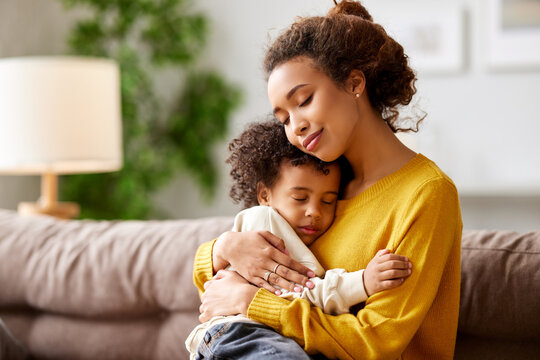 Loving afro american mom cuddling with little kid son while relaxing on sofa