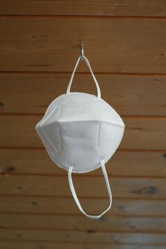 Eine FFP2 Schutzmaske (zum Schutz vor Covid-19) ist zum Trocken /Lüften an einem Haken aufgehängt