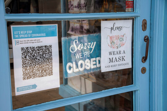 England, UK. 2021.  Shop door with closed sign and Test and Trace Covid-19 QR Code for NHS app. Wear a Mask sign.