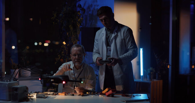 Adult repairman fixing drone in office talking to colleague cooperating. Handsome young man in lab coat flying drone technology testing in research office. Teamwork.