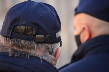 Fototapeta Polski policjant w niebieskim mundurze z napisem policja.  obraz