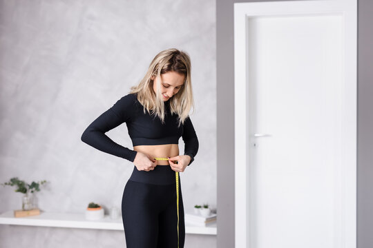 Slim young woman measuring her thin waist with a tape measure at home in the living room wearing a sport outfit, copy space