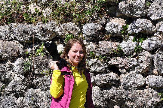 Girl with a camera near a stone wall
