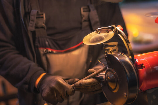 A mechanic in a gray jumpsuit processes a metal part on a grinding machine