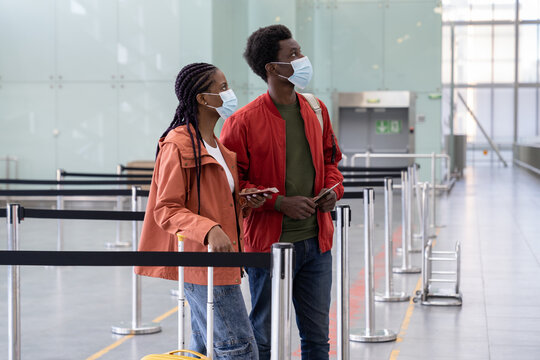 African couple wear protective medical masks wait for boarding on plane in airport in covid-19 pandemic. Safe travel during coronavirus. Young black man and woman before flight to honeymoon vacation