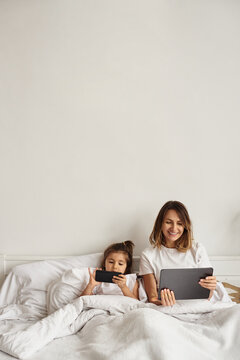 mom works at the computer while playing with her daughter