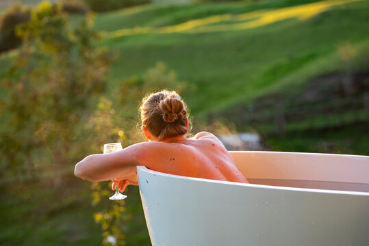 Woman in outdoor bath watching sunset