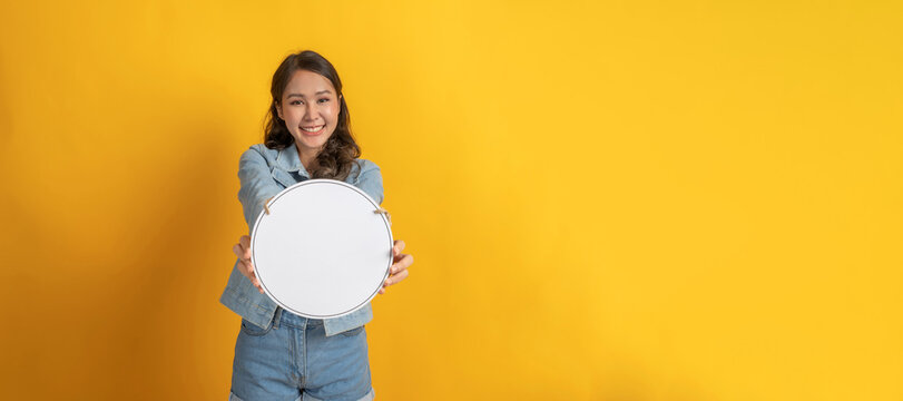 young asian pretty woman in casual clothing smiling and hold white blank sign board with copy space area for text on yellow panoramic wide background, online marketing and advertisement concept