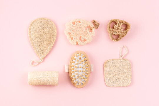 Natural hygiene products, wooden anti cellulite massager, loofah sponge, eco friendly, zero waste product. Reusable items for beauty treatment from organic biodegradable material on pink background