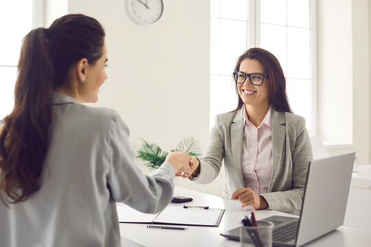 Happy bank worker, realtor or loan advisor shaking hands with grateful client. Young woman making deal with business partner. Office meeting, respect, appreciation, cooperation, transaction, agreement