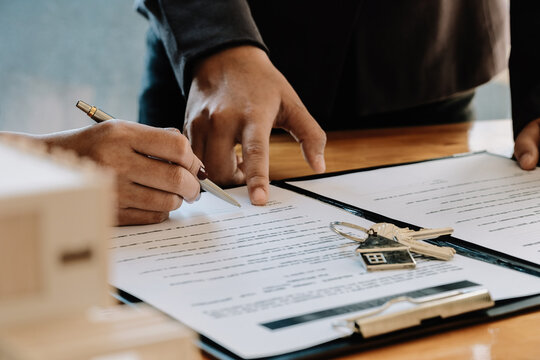 Real estate agent offer hand for customer sign agreement contract signature for buy or sell house. Real estate concept contact agreement concept