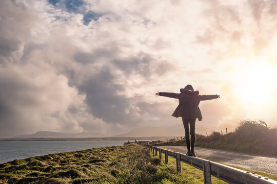 Teenager girl walking on a metal safety barrier by the ocean with hands up in the air. County Sligo, Ireland, Warm sunny day with beautiful cloudy sky. Travel and outdoor activity concept.