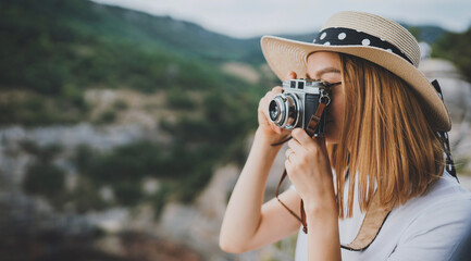 Fototapeta young blonde girl in summer hat takes photo on retro camera on background panorama horizin mountain landscape, hipster tourist enjoys hobby of photographer  leisure in summer nature empty space obraz