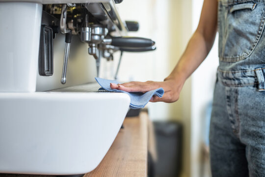 Womans hand with napkin sliding on coffeemaker