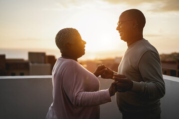 Happy black couple dancing outdoors at summer sunset - Focus on man face