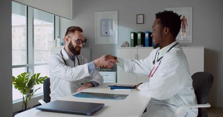 Medical team discussing medical test result in hospital office.