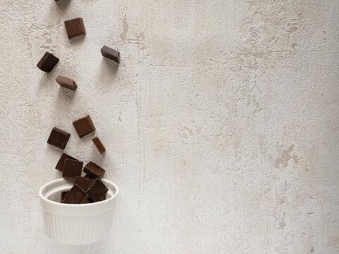白いラムカンに向かって落ちるチョコレート