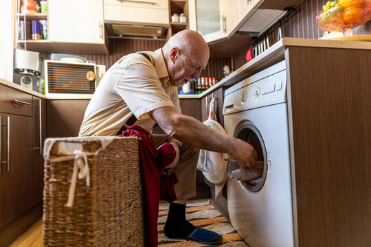 Senior man doing the laundry at home
