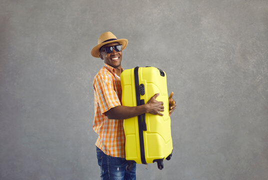 Cheerful man going on summer vacation. Portrait of happy smiling black tourist in glasses, sun hat and orange shirt holding yellow travel suitcase standing on gray studio background