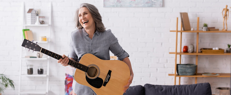 happy mature woman with grey hair standing with acoustic guitar in living room, banner
