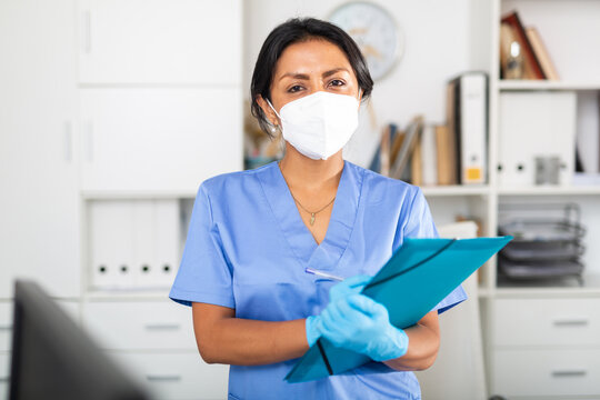 Portrait of latin american female doctor in surgical face mask meeting patient in medical office, filling out medical form at clipboard