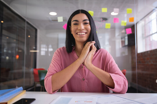 Happy mixed race businesswoman sitting at desk while having a video call smiling