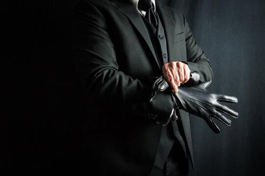 Portrait of Businessman in Dark Suit Pulling on Black Leather Gloves. Well Dressed Mafia Hit Man. Gentleman Assassin.