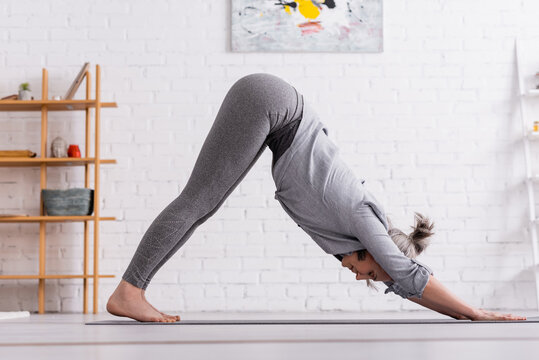 middle aged woman in downward facing dog pose practicing yoga on mat at home