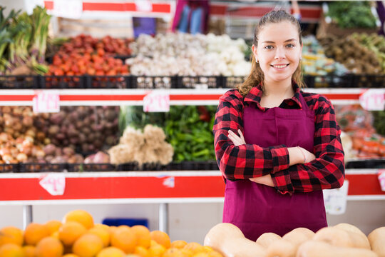 Portrait of smiling girl working saleswoman standing at counter in store