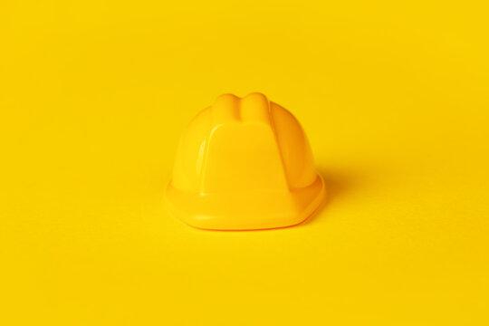 Yellow plastic hardhat over yellow background