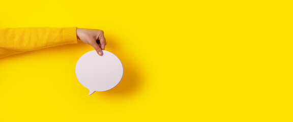 Talk bubble speech icon in hand over yellow background, panoramic layout