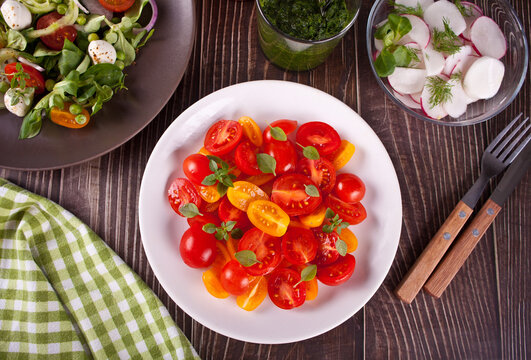 salads of fresh cherry tomatoes, mozzarella, basil and other greens on the dinner table