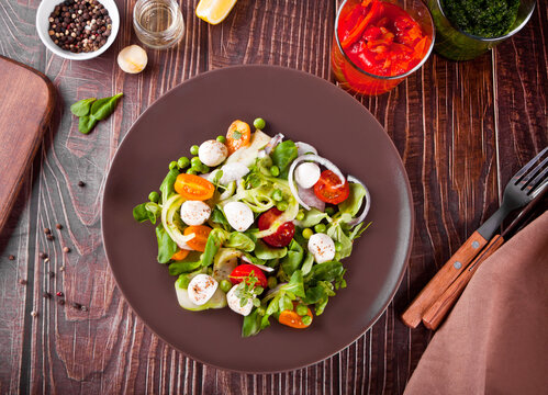 salad of fresh cherry tomatoes, mozzarella, basil, radish and other greens on the dinner table