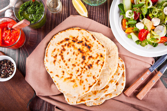 Homemade Indian naan flatbread with fresh salad and dips on the dinner table. Top view.