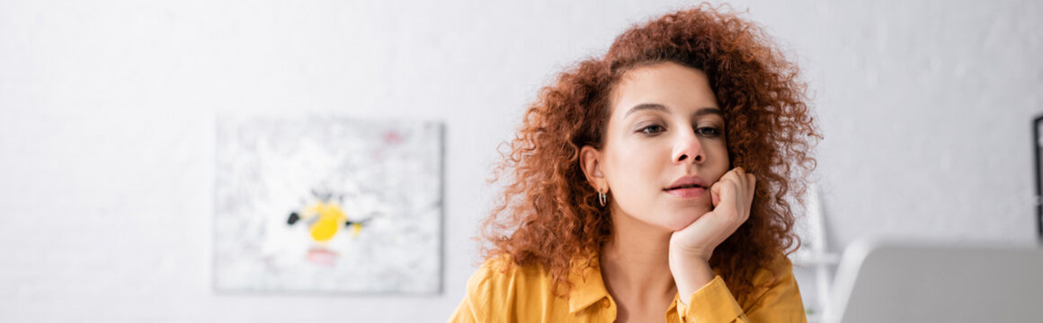 thoughtful woman with curly hair looking away at home, banner