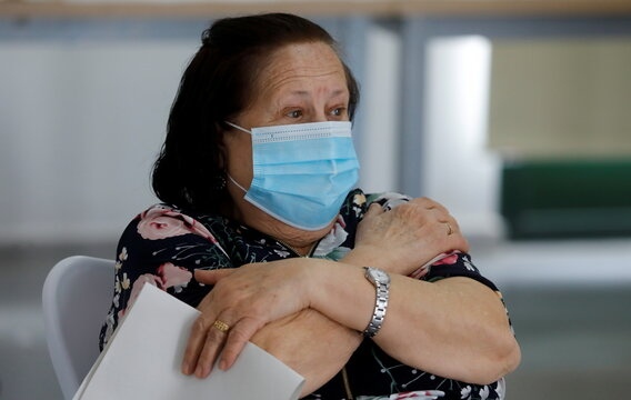 A woman touches her arm as she waits after receiving the dose of Johnson & Johnson's coronavirus disease (COVID-19) vaccine at a vaccination centre in Ronda