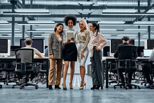 A group of young successful business women working together standing in the middle of the office and looking at a tablet. In the background are colleagues working on computers.