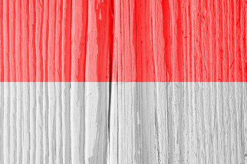 The flag of Indonesia on dry wooden surface, cracked with age. Light pale faded paint. Background, wallpaper or backdrop with Indonesian national symbol. Old wood. Hard sunlight with shadows