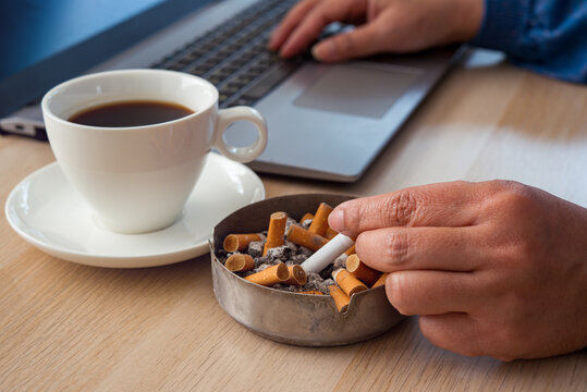 Stress woman smoking cigarette drinking black coffee working under pressure from home on laptop. Bad habits concept.