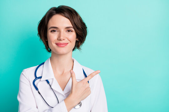 Photo of young woman doctor happy positive smile indicate finger empty space ad advice clinic isolated over teal color background