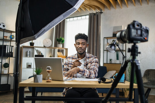 Young afro-american streamer in casual outfit sitting at table and using professional video camera, laptop and soft box. Concept of social networks and trends.