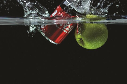 Close up view of cans of Coca Cola and apple falling into water with spray.