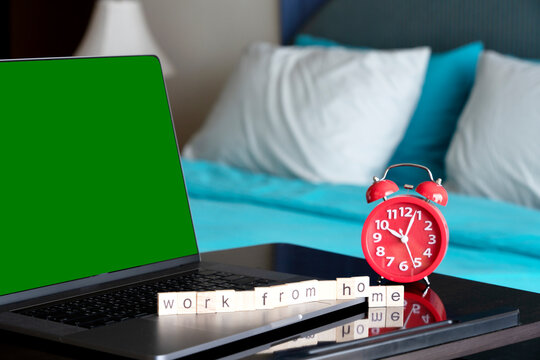 Laptop with WFH wording and red Alarm clock 10 O'clock. Teamwork  zoom Video conference calling on green screen. Remote monitor webcam team work. Distance webinar online working concept.